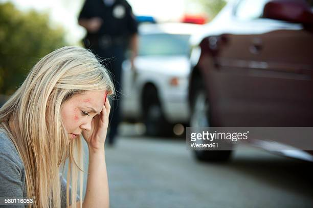 USA, woman sitting on ground with injury after accident