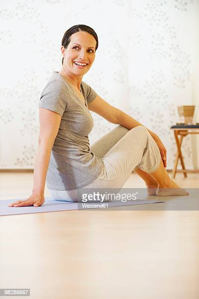 Woman sitting on gym mat, smiling, portrait