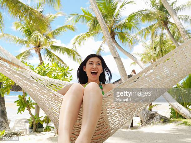 woman sitting on hammock, laughing - guam stock pictures, royalty-free photos & images