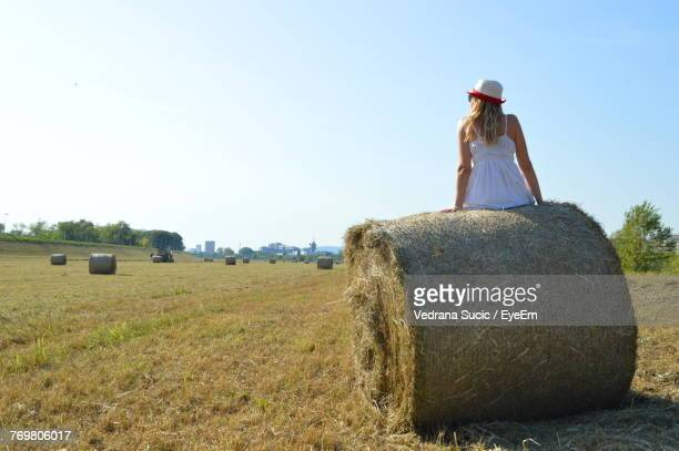 Woman Sitting On Hay Bales At Field Against Sky