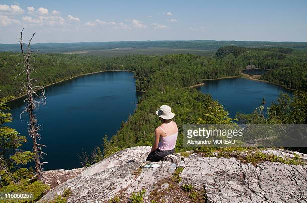 woman sitting on high rocks in canadian wilderness - lake superior provincial park stock pictures, royalty-free photos & images