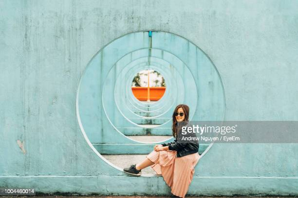 woman sitting on hole in wall - circle stock pictures, royalty-free photos & images