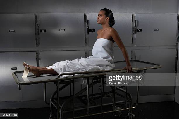 Woman sitting on hospital trolley, side view