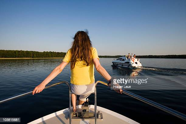 Woman sitting on houseboat bow,  Lake Zotzensee, Mecklenburgian Lake District.