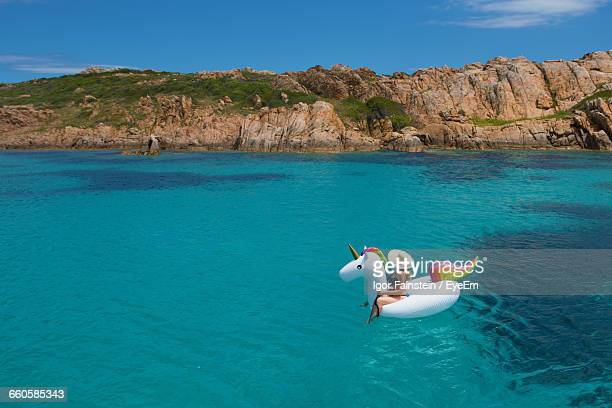 Woman Sitting On Inflatable Unicorn In Aegean Sea Against Sky