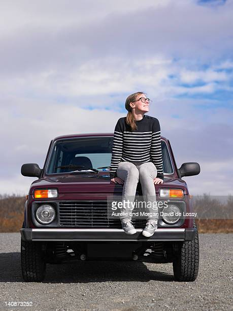 Woman sitting on jeep outdoors