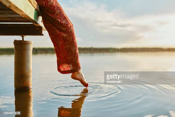 woman sitting on jetty at a lake at sunset touching the water with her foot - jetty stock pictures, royalty-free photos & images
