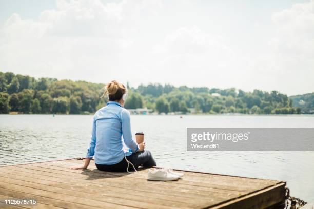 woman sitting on jetty at a lake with headphones and takeaway coffee - north rhine westphalia stock pictures, royalty-free photos & images