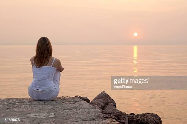 Frau sitzt auf Anlegesteg