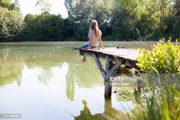 woman sitting on jetty with two fishing rods - freizeitaktivität stock-fotos und bilder
