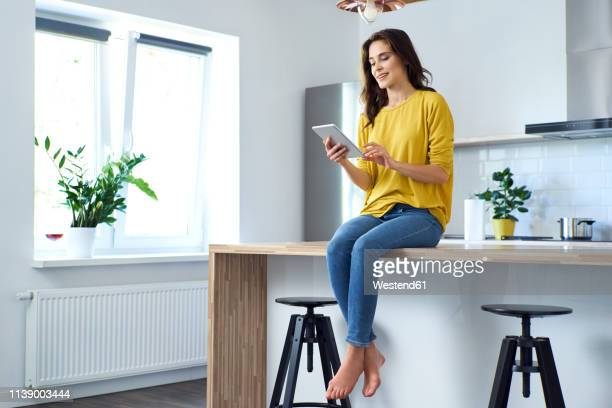 woman sitting on kitchen counter at home, using digital tablet - tablet benutzen stock-fotos und bilder