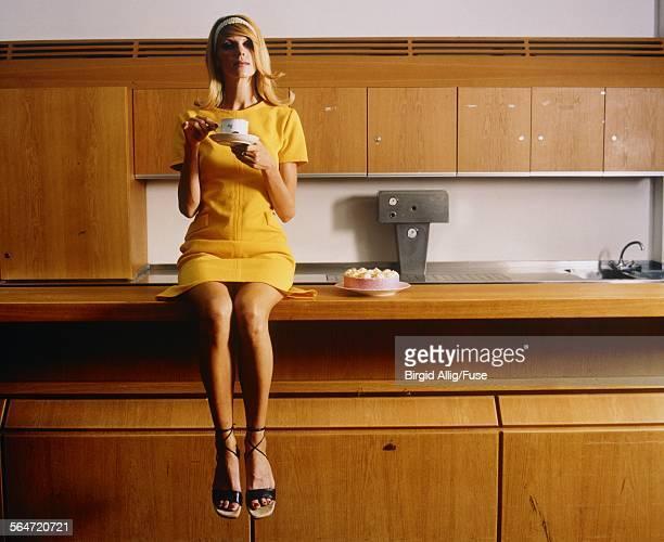 Woman Sitting on Kitchen Counter