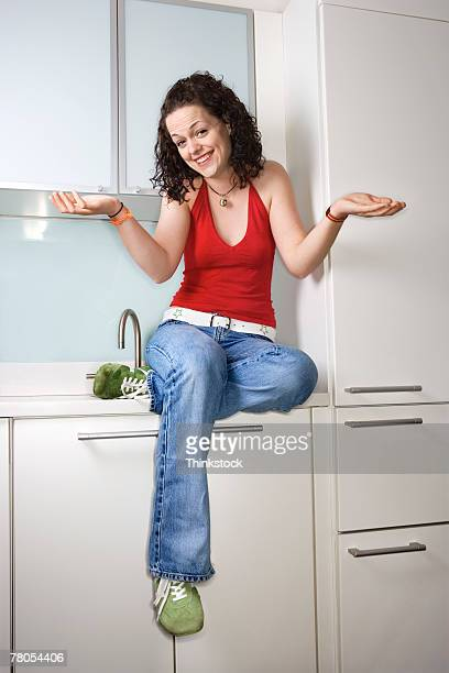 Woman sitting on kitchen counter shrugging