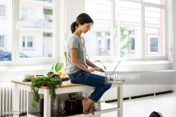 woman sitting on kitchen table, searching for healthy recipes, using laptop - searching stock pictures, royalty-free photos & images