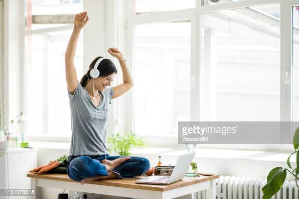 woman sitting on kitchen table, searching for healthy recipes, using laptop - körperbewusstsein stock-fotos und bilder