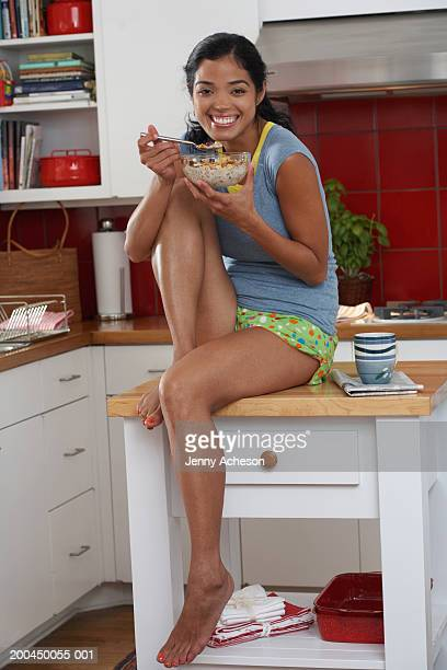 Woman sitting on kitchen worktop eating bowl of cereal, smiling