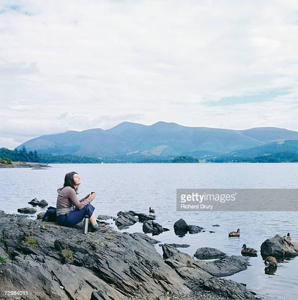 woman sitting on lake shore, mountains far shore - richard drury stock pictures, royalty-free photos & images