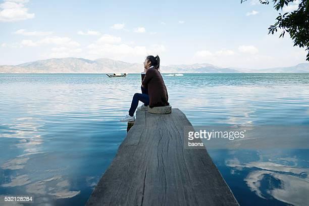 Frau sitzen auf einem See Steg