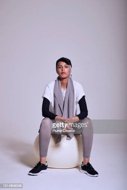 Woman sitting on large fitness ball