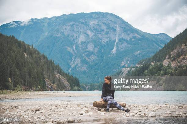 woman sitting on log by lake against mountain - kerry estey keith stock photos and pictures