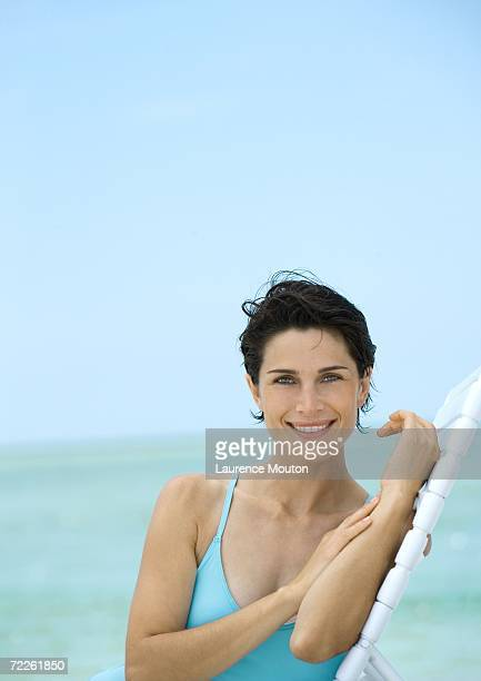 woman sitting on lounge chair on beach - cheveux courts photos et images de collection