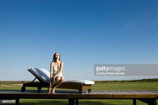 Woman sitting on lounge chair outdoors, looking up dreamily