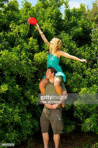 Woman sitting on man's shoulders holding