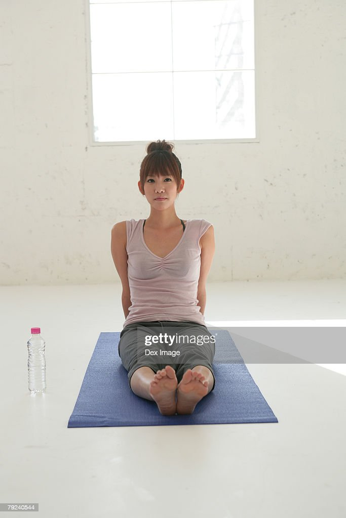 Woman sitting on mat, legs stretched : Stock Photo
