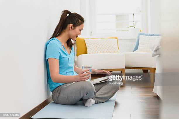woman sitting on mat using digital tablet - tracksuit bottoms stock pictures, royalty-free photos & images