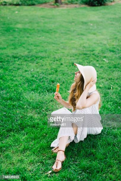 Woman sitting on meadow earing popsicle