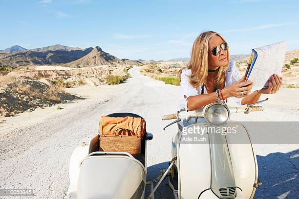 Woman Sitting on motorbike with map