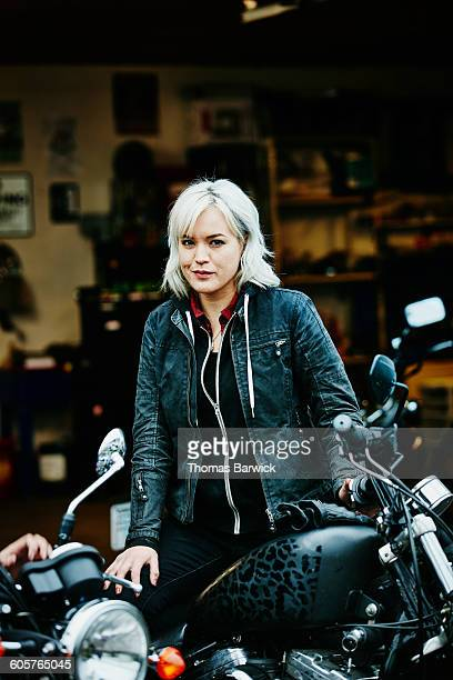 Woman sitting on motorcycle with helmet off