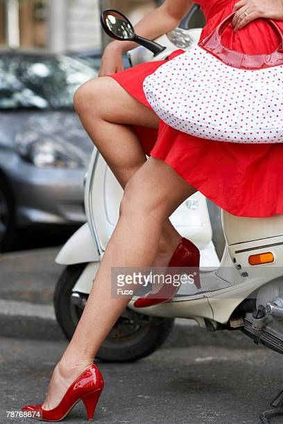 woman sitting on motorscooter - legs and short skirt sitting down stock photos and pictures