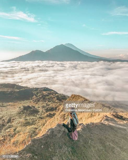 woman sitting on mountain against cloudscape - kintamani district stock pictures, royalty-free photos & images