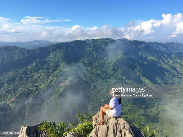 woman sitting on mountain against sky - cebu stock photos and pictures
