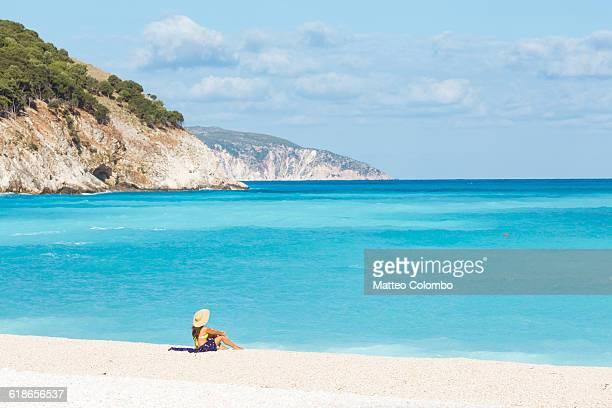 Woman sitting on Myrtos beach. Kefalonia, Greece
