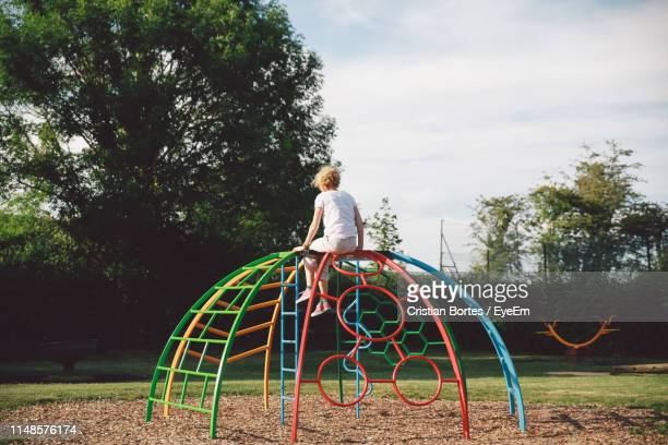 woman sitting on outdoor play equipment at playground - britain playgrounds stock pictures, royalty-free photos & images