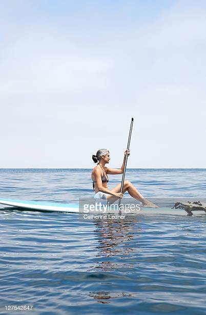 woman sitting on paddle board in the ocean - paddleboard stock photos and pictures