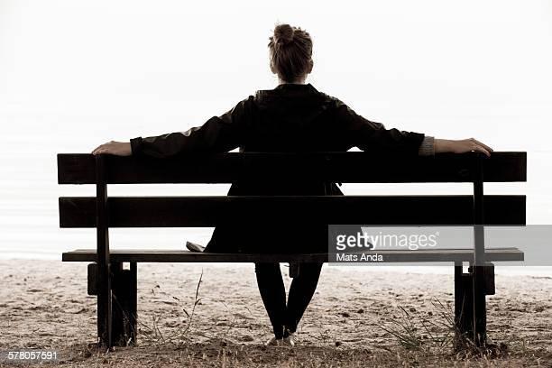 Woman sitting on park bench on beach