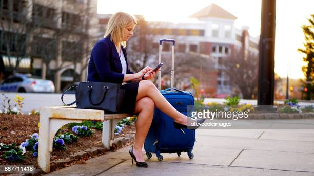 Woman sitting on park bench using phone.