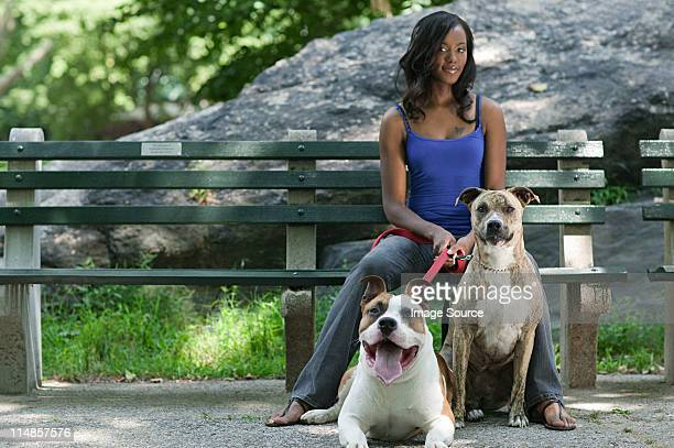 Woman sitting on park bench with her two dogs