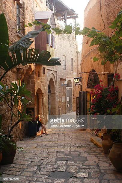woman sitting on passage of traditional house in alley - tel aviv stock pictures, royalty-free photos & images