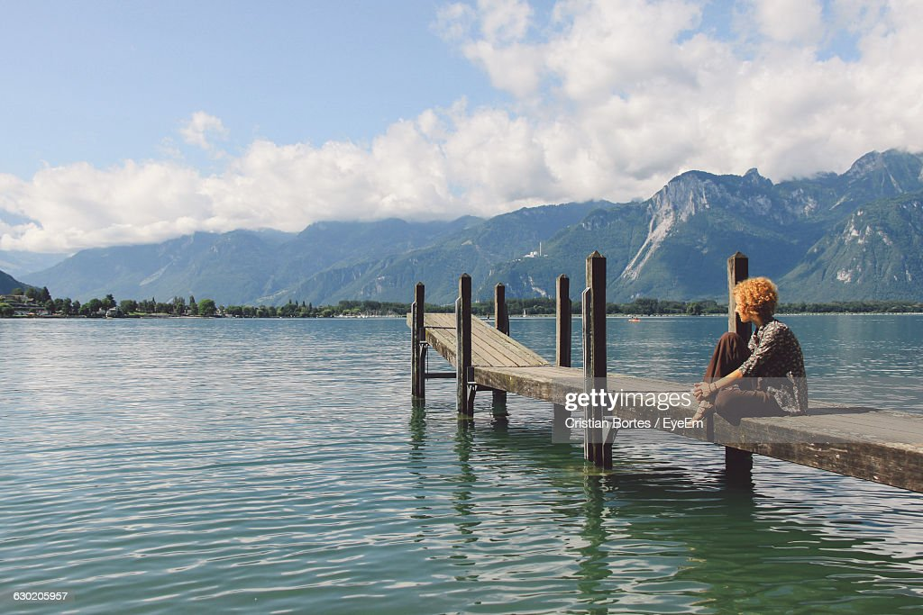 Woman Sitting On Pier Over Lake Against Sky : Stock Photo