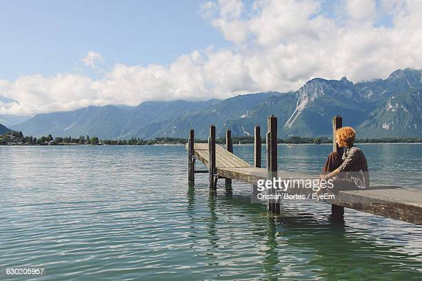 Woman Sitting On Pier Over Lake Against Sky
