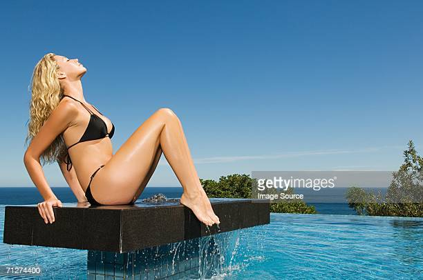 Woman sitting on platform in pool