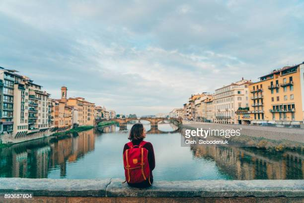 woman sitting on ponte veccio and looking at view - ita foto e immagini stock