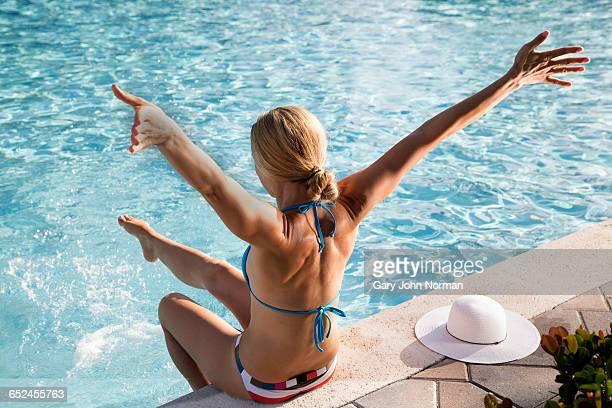 woman sitting on pool edge with arms outstretched - femme blonde en maillot de bain vue de dos photos et images de collection