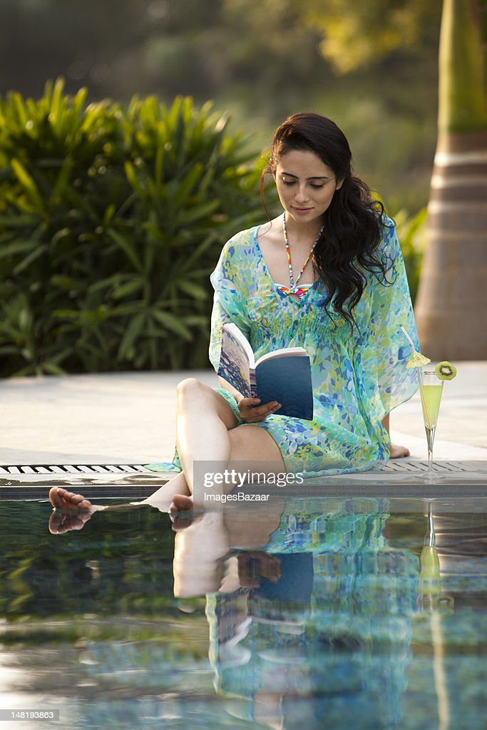 Woman sitting on poolside and reading book : Stock Photo