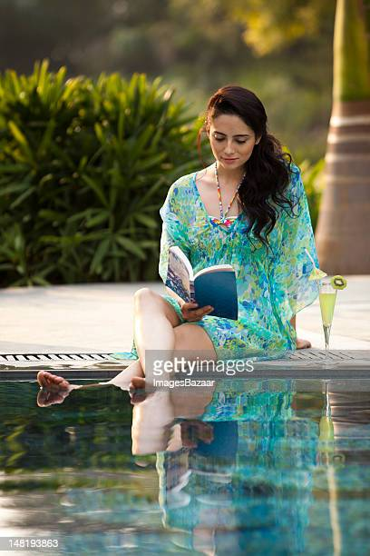 Woman sitting on poolside and reading book