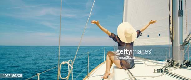 Woman sitting on prow of boat, Croatia